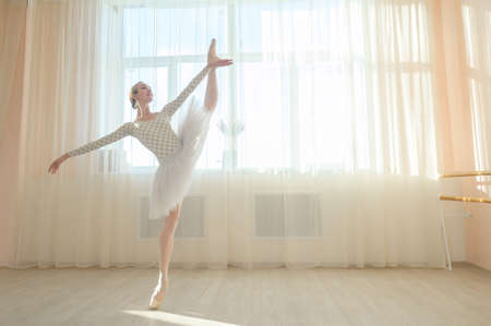 Beautiful ballerina in body and white tutu is training in a dance class. Young flexible dancer posing in pointe shoes. 写真素材