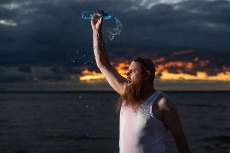 A humorous portrait of a brutal man pouring soda from a bottle on the beach at sunset
