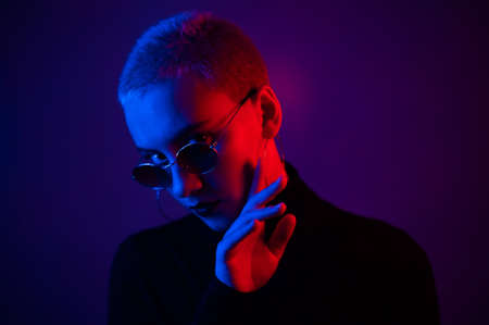 Portrait of a beautiful young woman with short hair in sunglasses in neon light 写真素材