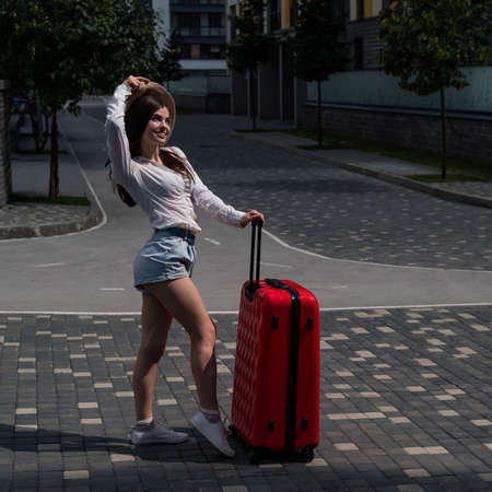 Beautiful caucasian brunette woman in a hat posing with a suitcase on a city street.