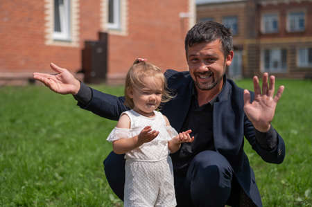 Caucasian man in a black suit walks with his little daughter