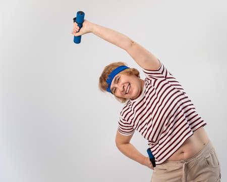 Elderly caucasian woman doing side bends with dumbbells in studio. 写真素材