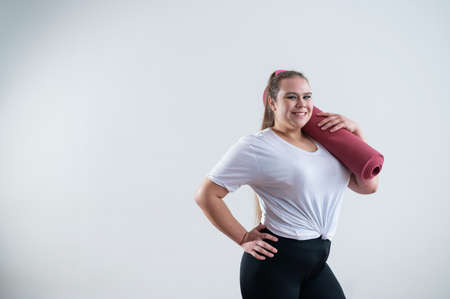 Young fat caucasian woman holding a sport mat. Charming plus size model in sportswear stands on a white background 写真素材