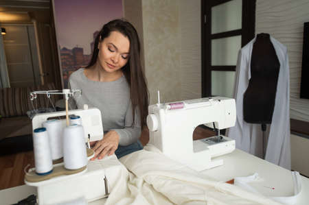 Caucasian woman sews to order at home. Work space of a seamstress in the living room