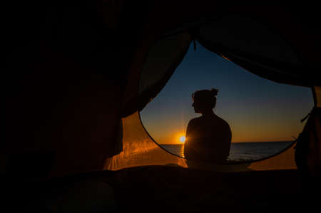 A woman and a dog are resting in a tent in nature at sunset. The girl and Jack Russell Terrier set up camp on the river bank