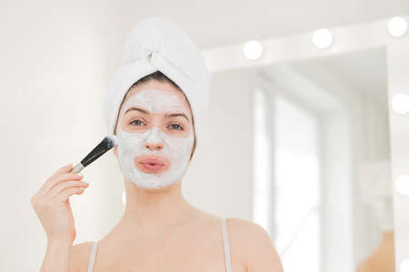 Beautiful caucasian woman with a towel on her hair applies a clay face mask. Taking care of beauty at home