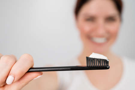 A woman with a perfect smile holds a toothbrush with toothpaste in the foreground. Oral hygiene 写真素材