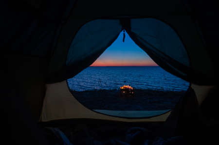 View from a tourist tent on bonfire on the seashore at sunset. 写真素材