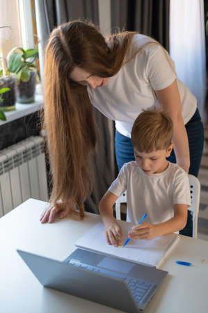 Caucasian woman helps her son learn lessons. Caring mother checks the childs homework. Study at home during quarantine.