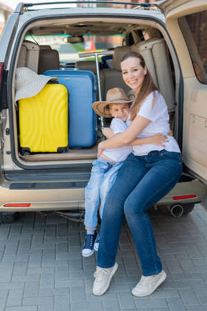 European woman sitting with her son in the trunk of an SUV. Beautiful happy mother loving hugs son. Yellow luggage for summer vacation by car. Holidays with the whole family.