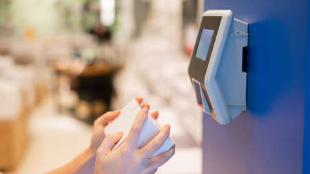 A faceless woman uses a price scanner on the wall