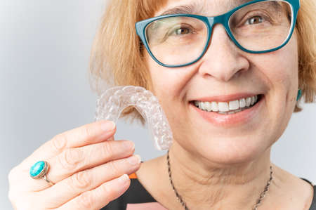 A happy elderly woman puts on transparent removable braces. Cosmetic dentistry for all ages 版權商用圖片
