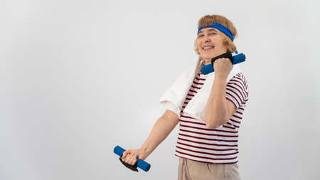 An elderly woman with a blue bandage on her head trains with dumbbells on a white background