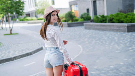 Young caucasian woman in a hat and shorts stands on the street with a red suitcase. 版權商用圖片