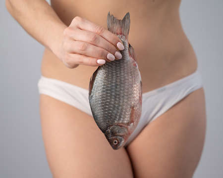A woman in shorts is holding a fish. Feminine hygiene and health concept. 版權商用圖片