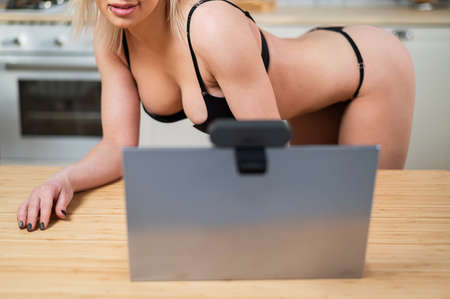 A girl in underwear flirts on an online video connection on a laptop. Woman working as a web cam model
