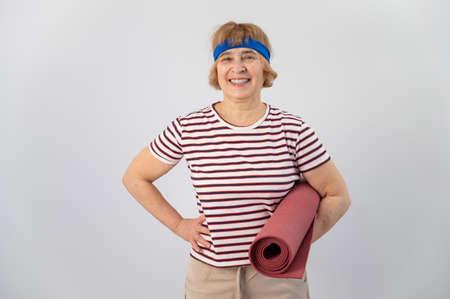 Elderly caucasian woman holding folded yoga mat in studio.