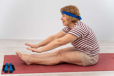 Happy elderly woman doing stretching on white background. Copy spase