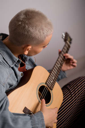 Young short-haired blonde woman learning to play acoustic guitar on white background. 版權商用圖片