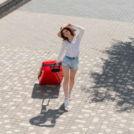 Happy caucasian young woman in hat and shorts holding a large red suitcase at an open age