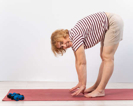 Elderly woman makes bends on a white background. Old lady doing health stretching exercises 版權商用圖片