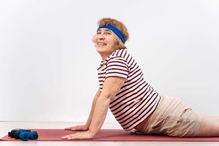 Elderly woman doing exercises in the studio on a white background. The old lady is doing fitness for health