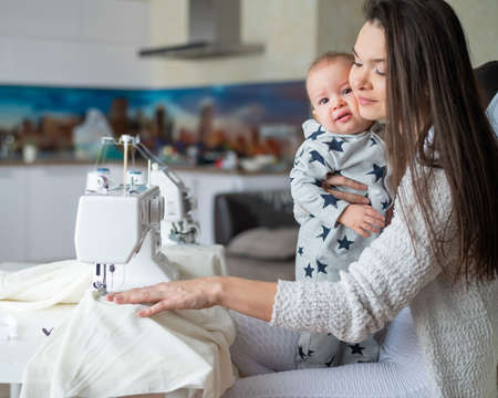 A young woman sews in the kitchen and holds a small child. Mom teaches her little son to sew on a sewing machine. Self-isolation homework