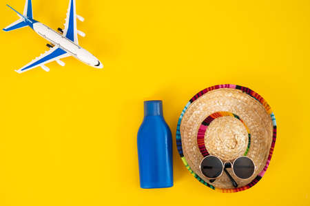 Airplane sombrero sunglasses and a tube of sun cream on a yellow background. Summer vacation concept.