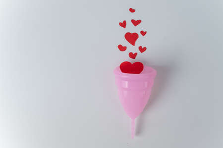 Pink menstrual cup and hearts imitating blood on a white background. Reusable personal hygiene product for women. Copy space