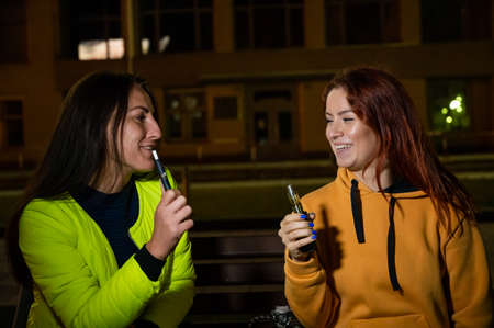 Two caucasian women smoke vape and hookah outdoors at night. 版權商用圖片