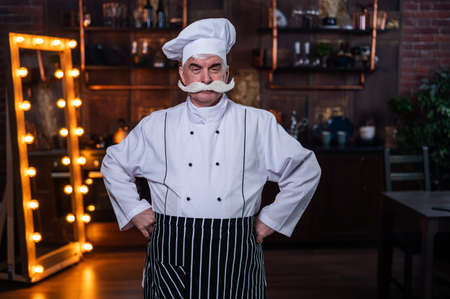 A friendly elderly male professional chef wearing an apron and a hat