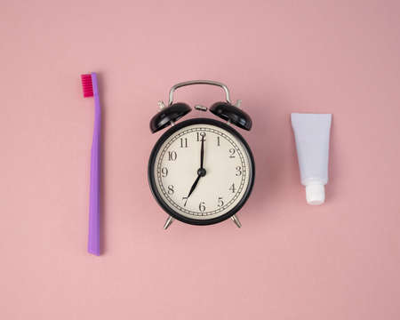 Toothbrush, tube of toothpaste and alarm clock on a pink background. Time to brush your teeth. 版權商用圖片