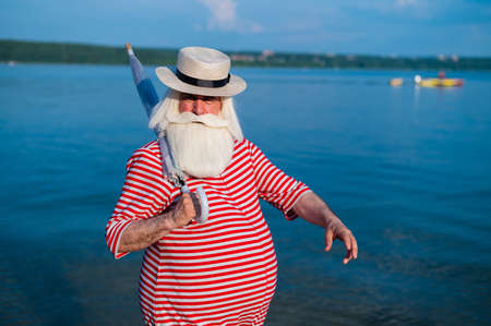 An elderly man in a classic bathing suit walks along the beach with an umbrella on a hot summer day