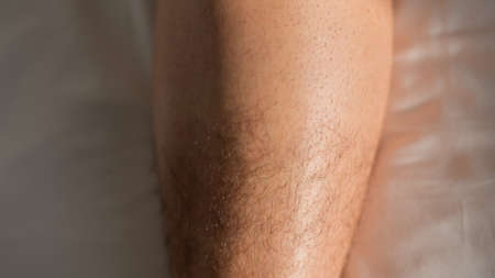 Close-up of a shaved half male leg. 스톡 콘텐츠