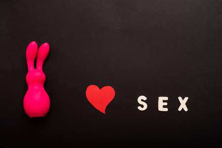 Clitoral vibrator in the form of a pink rabbit, a heart and the inscription sex on a black background. Copy space.