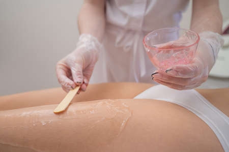 The master applies the anesthetic gel with a spatula to the womans legs before laser hair removal. Permanent hair removal with a device in the clinic