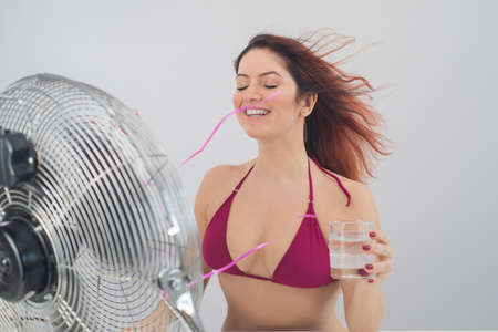 Red-haired smiling woman in a bikini drinks a cold drink and enjoys the blowing wind from an electric fan on a white background. Climate control on a hot summer day