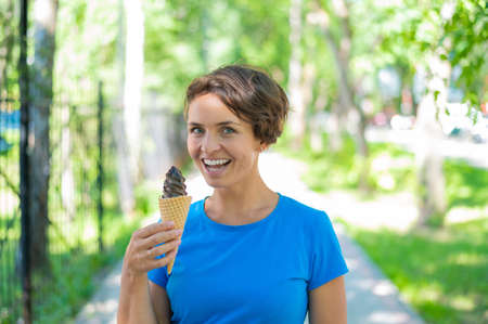 Happy caucasian girl in blue dress eats chocolate ice cream cone outdoors. Emotional excited short-haired woman enjoying a chilling gelato on a hot summer day in the park.