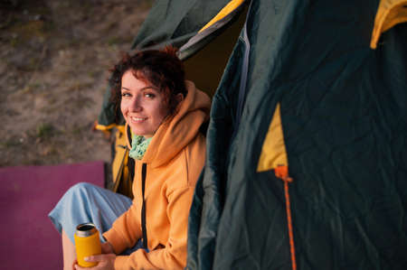 A pensive Caucasian woman in a sweatshirt sits in a tourist tent and drinks from a mug. Rest at nature.