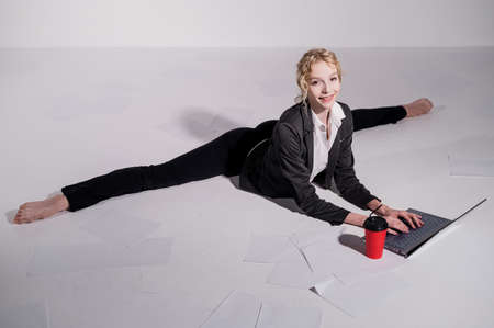 A ballerina dressed in a business suit sits in a middle twine, works at a laptop and drinks coffee. Flexible woman works at the computer 스톡 콘텐츠