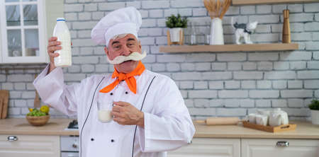 An elderly milkman holds a bottle of cows milk in the kitchen. A man in a chefs hat is cooking 스톡 콘텐츠