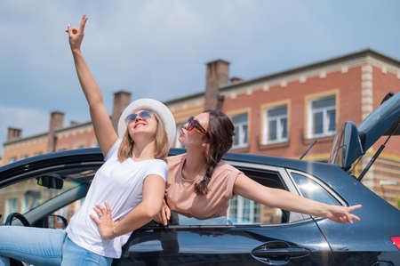 Two women are fooling around at the car. Girlfriends travel by car