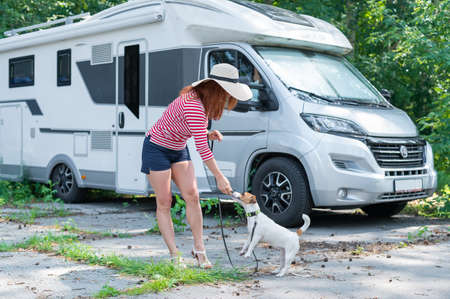 Caucasian red-haired woman in a straw hat and striped sweater walks with a small dog in front of a mobile home. Travel in a camper van with your pet