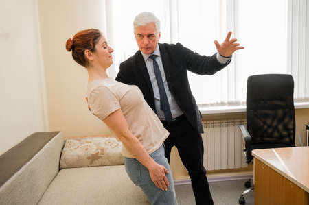 Mature gray-haired man hypnotizes Caucasian woman during hypnotherapy session. The psychologist uses alternative treatments for the subconscious mind 스톡 콘텐츠