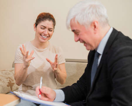 Mature gray-haired male psychotherapist with clipboard in session with female patient. Smiling caucasian woman at a psychologist appointment.