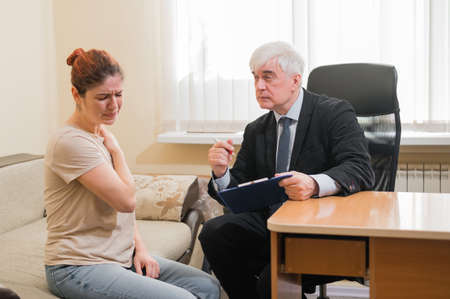Caucasian woman crying at psychotherapist session. Male psychiatrist taking notes on a clipboard during a personal consultation
