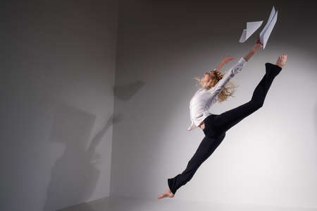 A graceful ballerina in a business suit throws documents in the studio. Business woman dance barefoot on a white background 스톡 콘텐츠