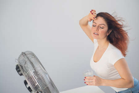 A red-haired Caucasian woman chills by the electric fan and drinks a cold drink. Climate control in the apartment 스톡 콘텐츠