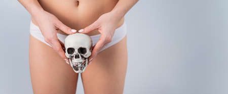 Faceless woman in underpants holding a skull on a white background. 스톡 콘텐츠