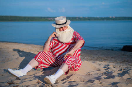 Portrait of an elderly man wearing in a classic swimsuit and Boater on the beach.